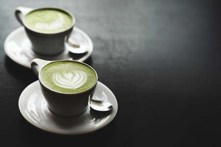 59153510 - two cups of matcha latte with latte art on black table. top view.